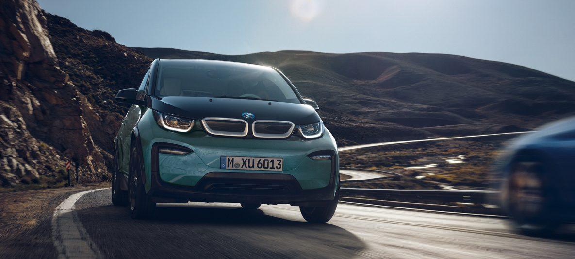 BMW i3 I01 2018 Jucarobeige mit Akzent Frozen Grey metallic Seitenansicht fahrend in urbaner Kulisse
